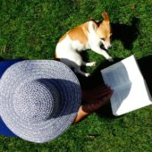 ariel view of person with sun hat reading outdoors next to a dog